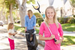 mother and her daughters picking up trash around the suburbs