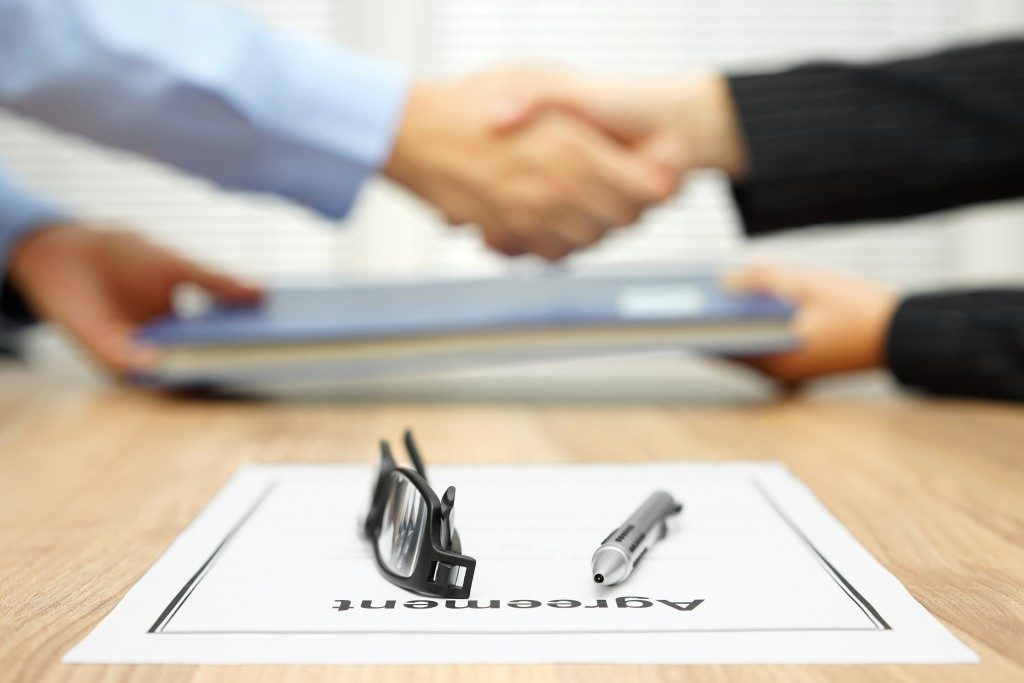 Woman shaking hands after signing an agreement