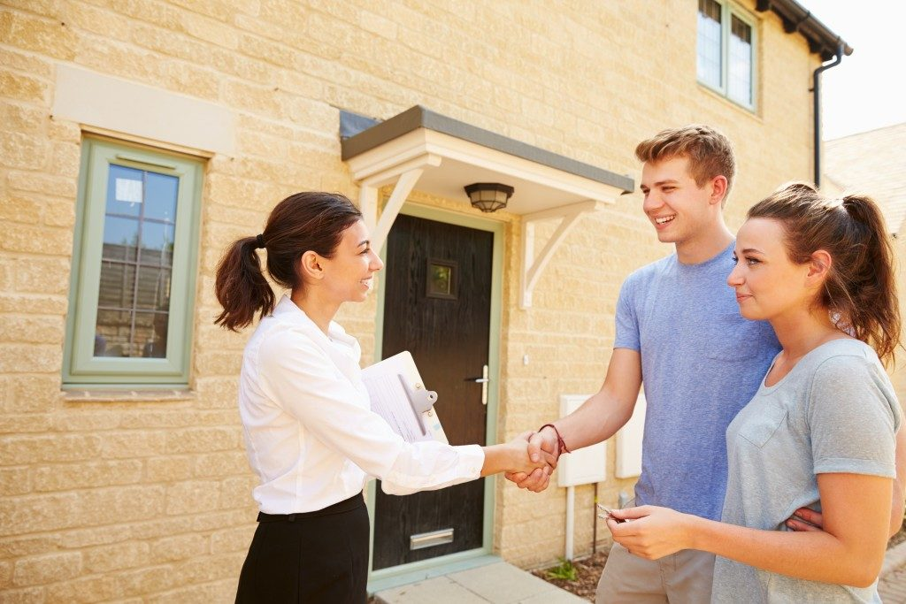 Agent shaking hands with new property owner