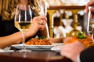 Woman with a plate of pasta and glass of wine