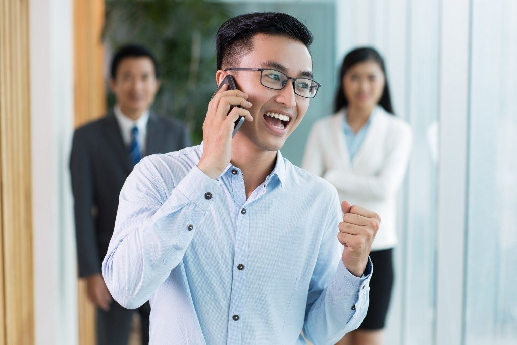 Happy businessman talking on phone and smiling