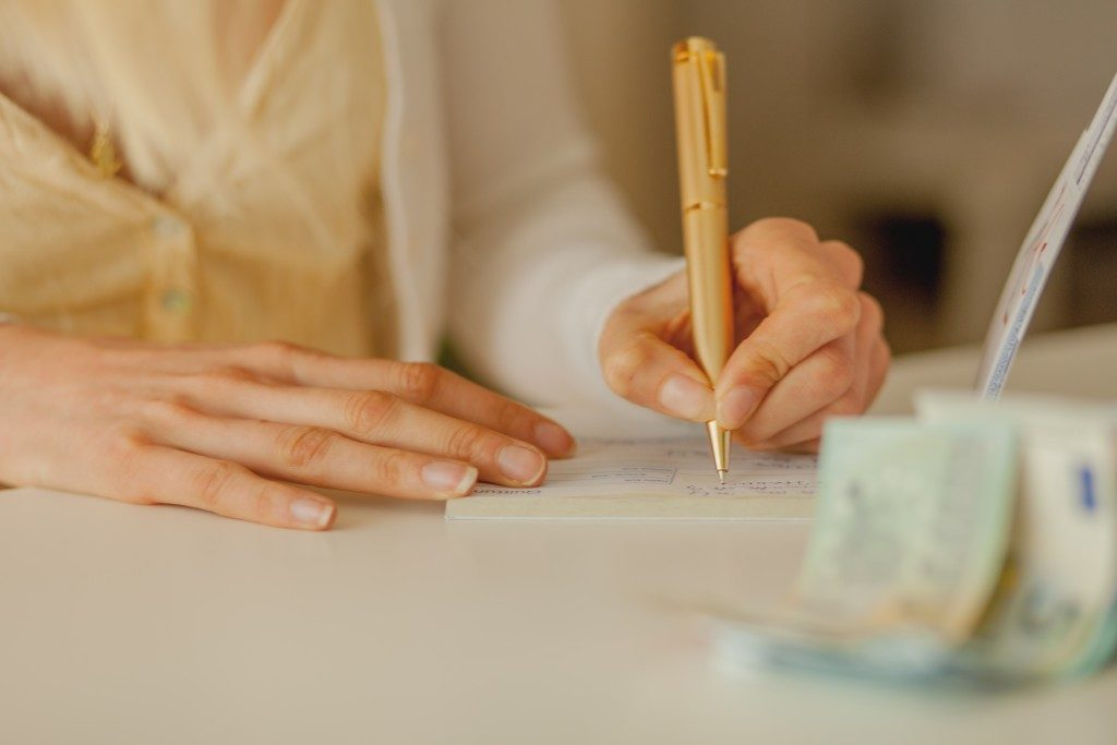 hand of a woman signing a cheque