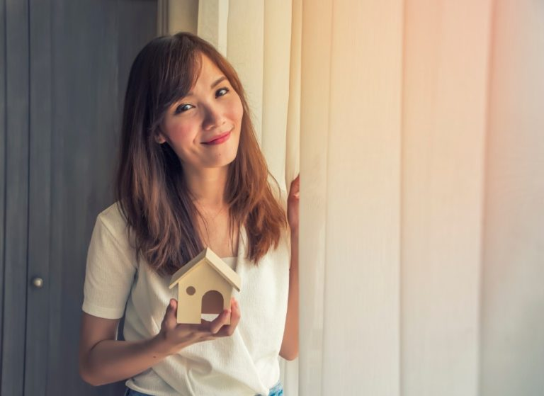 woman holding a miniature house