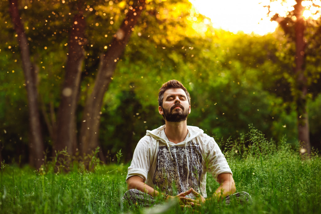 man meditating in forest concept